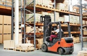 Man driving a rental forklift in a warehouse storing pallets