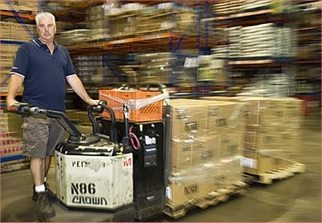 Order picker picking an order riding on a Crown Pallet Jack.